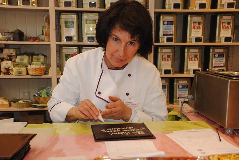 Celina Pastewski verziert eine von zahlreichen Schokoladentafeln. Sie arbeitet seit 20 Jahren bei Wagner Pralinen und ist für Dekorationen zuständig.