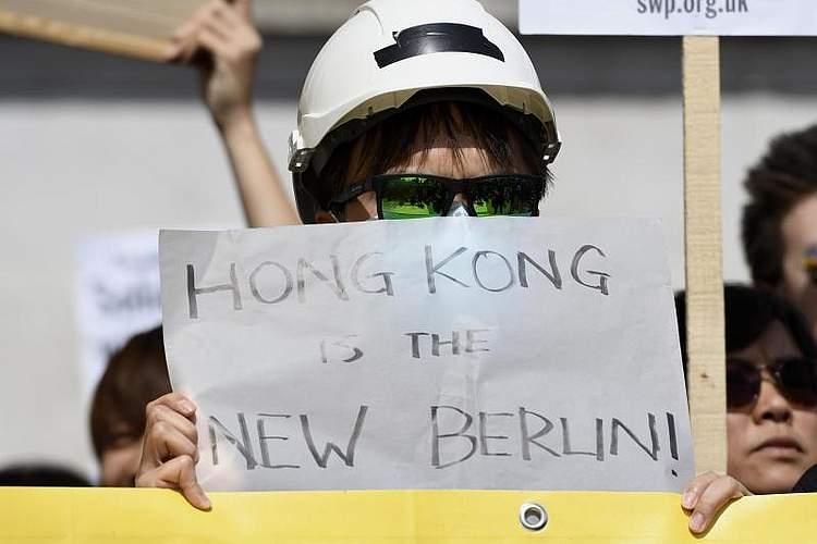 """Anhänger der Proteste in Hongkong halten ein Schild mit der Aufschrift """"Hong Kong is the new Berlin"""" (""""Hongkong ist das neue Berlin""""). Offenbar handelt es sich um eine Anspielung auf das alte West-Berlin, das einst von der repressiven DDRumgeben war. Foto: Andres Pantoja/SOPA Images via ZUMA Wire"""
