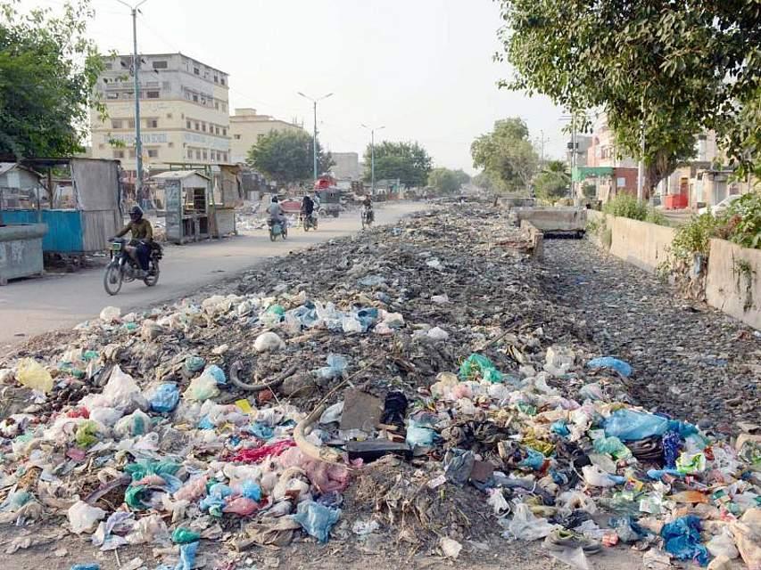 Ein Mann fährt in Karatschi in Pakistan auf einem Motorroller an einem großen Haufen Abfall vorbei, der am Straßenrand liegt. Foto: Ppi/PPI via ZUMA Wire