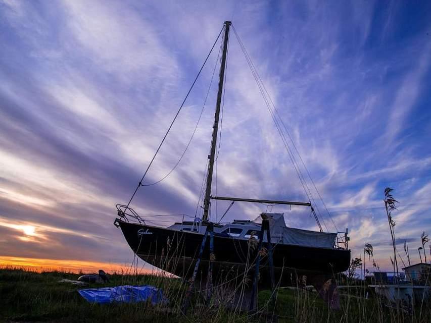 Ein Segelboot liegt am Greifswalder Bodden auf der Insel Rügen in einer kleinen Bootswerft auf dem Trockenen. Foto: Jens Büttner/dpa-Zentralbild/dpa
