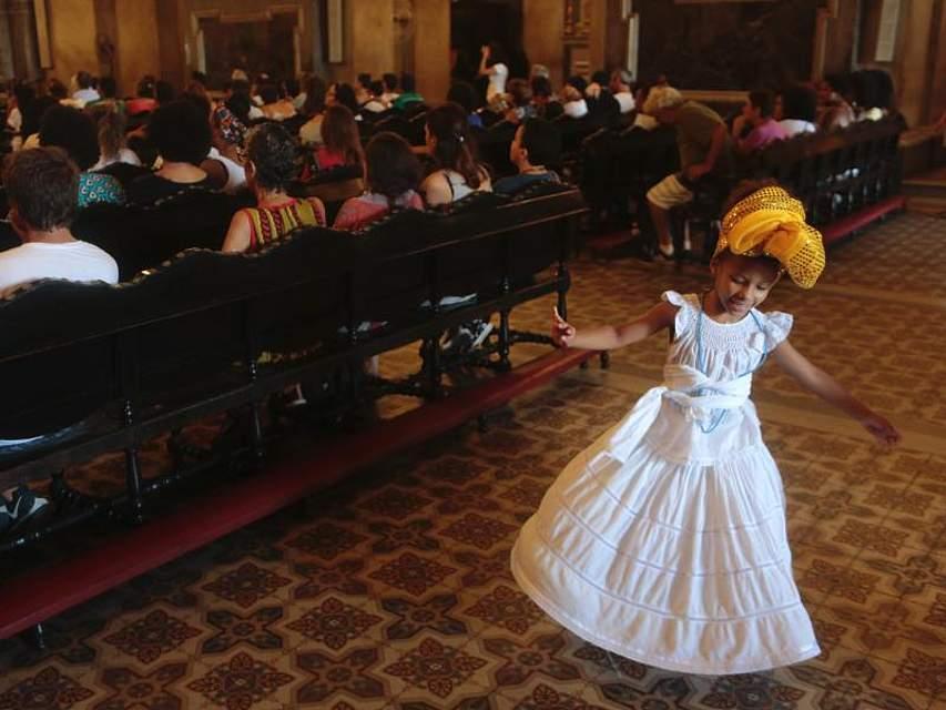 EinMädchen tanzt am Rande des Gottesdienstes zu Ehren der ermordeten Stadträtin Marielle Franco und ihres Fahrers ein Jahr nach ihrem Tod. Franco war ein Shootingstar der brasilianischen Linke. Foto: Ian Cheibub
