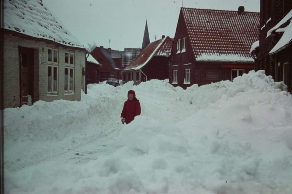 """Schneepracht auf der Klosterstraße in Meldorf. Hannelore Christiansen schreibt zu ihrem Foto: """"Mein Mann Ludwig Christiansen hatte zu der Zeit eine Woche Urlaub, in der er Kinderzimmermöbel für unsere Tochter bauen wollte. Daraus wurde dann nichts, weil er die ganze Woche im Feuerwehreinsatz war. Als leidenschaftlicher Feuerwehrmann in der Meldorfer Wehr war es seine Aufgabe – zusammen mit den Kameraden – Straßen zu räumen, Hefetransporte für die Bäckereien zu organisieren, damit für die Bevölkerung Brot gebacken werden konnte. Kranke mussten transportiert werden, ebenso wie Schwangere. Und viele andere Hilfsaufgaben mussten erfüllt werden. Mir fällt gar nicht mehr alles ein. Es blieb nicht eine freie Stunde, um an den Möbeln zu arbeiten, denn die Hilfe für andere Menschen stand absolut im Vordergrund. Während er von zu Hause abwesend war, versuchten unser Sohn und ich, uns zu unseren alten Nachbarn durchzuarbeiten, um dort eventuell Hilfe leisten zu können, zum Beispiel Einkäufe tätigen. Der Verkehr in der Klosterstraße kam zum Erliegen und unsere Tochter vergnügte sich zwischen den Schneemassen."""""""