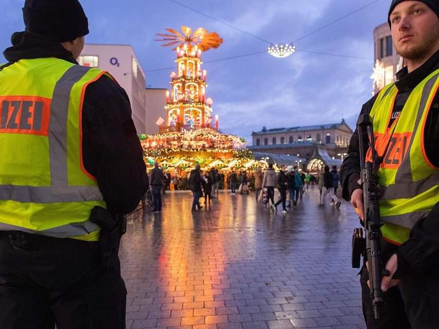 Schwer bewaffnete Polizisten mit Maschinenpistolen sichern die begehbare Pyramide auf dem Weihnachtsmarkt in Hannover. Foto: Julian Stratenschulte/dpa