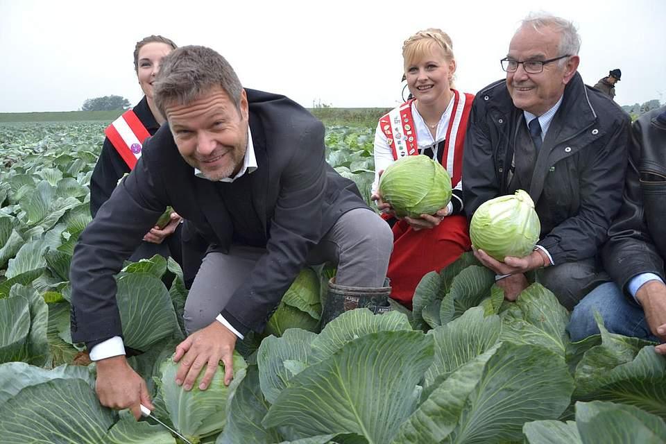 Landwirtschaftsminister Robert Habeck beim Kohlanschnitt in Nordermeldorf, mit den Kohlregentinnen Maren I., links, und Freia I. und Kreispräsident Hans-Harald Böttger.