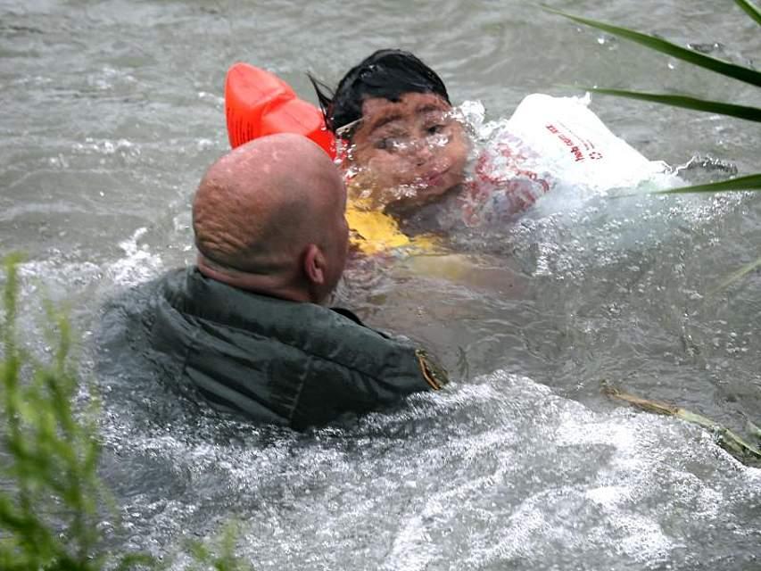 Ein US-Grenzschutzbeamter hilft einem Jungen aus Honduras, nachdem er von einem Floß in den Grenzfluss Rio Grande gefallen ist. Jedes Jahr fliehen Hunderttausende Menschen vor Gewalt und Armut in Mittelamerika und versuchen, in die USA zu gelangen. Foto: Bob Owen/The San Antonio Express-News