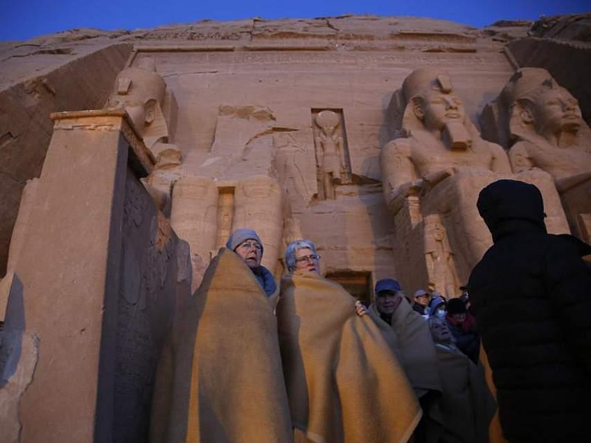 Touristen haben sich in Decken gewickelt, um ein besonderes Schauspiel zu beobachten, das nur zweimal im Jahr zu erleben ist. Dabei wirft die Sonne einen Lichtstrahl in eine ansonsten dunkle Kammer des 3200 Jahre alten Tempels bei Abu Simbel. Foto: Amr Nabil, AP